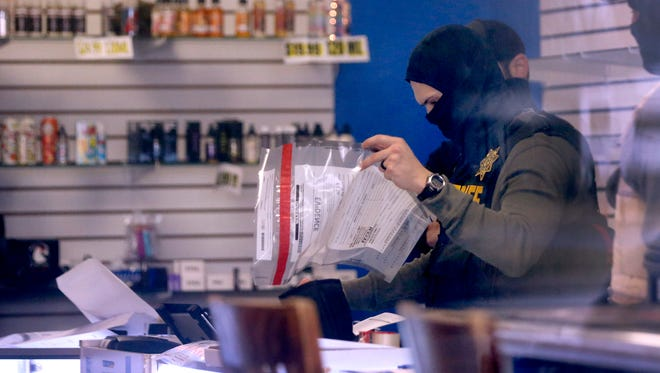 Authorities collect evidence at Vapesboro, one of 23 stores believed to be selling products containing CDB, a marijuana derivative, on Monday, Feb. 12, 2018.