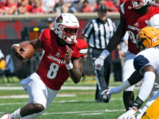 Louisville quarterback Lamar Jackson (8) attempts to turn upfield as he rushes against Kent State during the second half of an NCAA college football game, Saturday, Sept. 23, 2017, in Louisville, Ky. Louisville won 42-3. (AP Photo/Timothy D. Easley)
