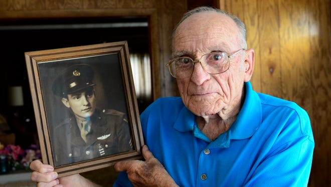 Charles Holcomb, 92, World War II Air Force veteran and prisoner of war, holds a picture of himself at 19 years old.
