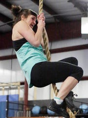 Denise Ristow, 62, of Sheboygan,lowers herself on the rope during her competition routine at Crossfit Eastern Ridge, Saturday, April 21, 2018, in Sheboygan, Wis.  Ristow is in the top 200 for the Crossfit Games.