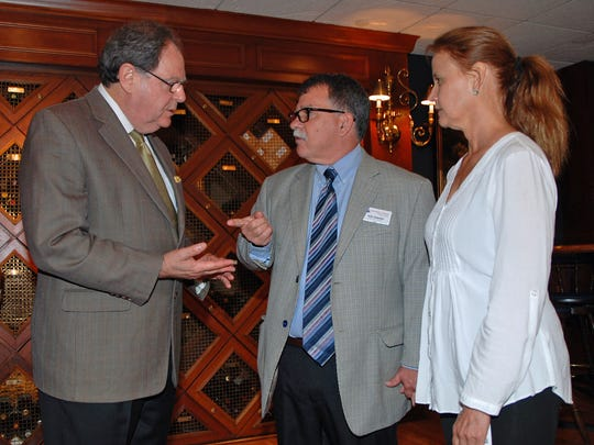 Guest speaker Jack Levine, left, talks with hosts and