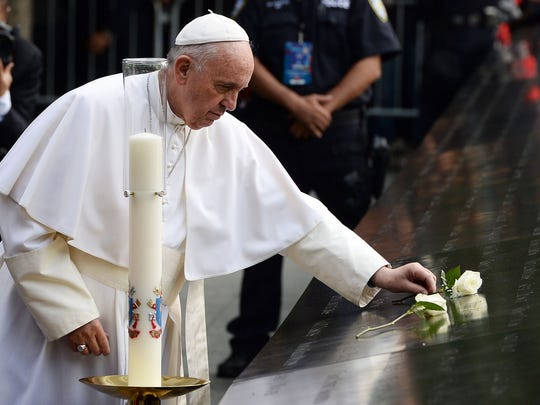 Pope Francis places a white rose on the names of the September 11 victims at the edge of the South Pool of the 9/11 memorial in New York on September 25, 2015. Pope Francis, who has built a wide global following for his reform-minded views, is on a five-day official visit to the US. AFP PHOTO/JEWEL SAMADJEWEL SAMAD/AFP/Getty Images