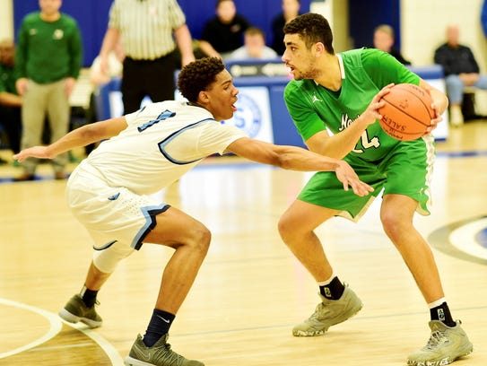 Novi's Tariq Woody (right) tries to find an opening