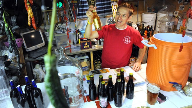 Ryan Will of Fond du Lac, displays some of his home brewed beer along with the tools and ingredients he uses to make it in his basement pub.. Saturday, January 14, 2012. The Reporter photo by Patrick Flood.