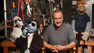 "Brian Henson, director of ""The Happytime Murders,"" sits with Phil Phillips, the puppet star of his R-rated film."
