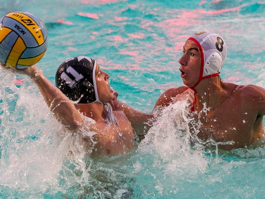Xavier Prep's Ryan Cenicola (No. 11) looks to pass as Palm Desert's August Sullivan defends during the DVL water polo championship match Saturday. Xavier Prep won 12-10 to win its first league title.
