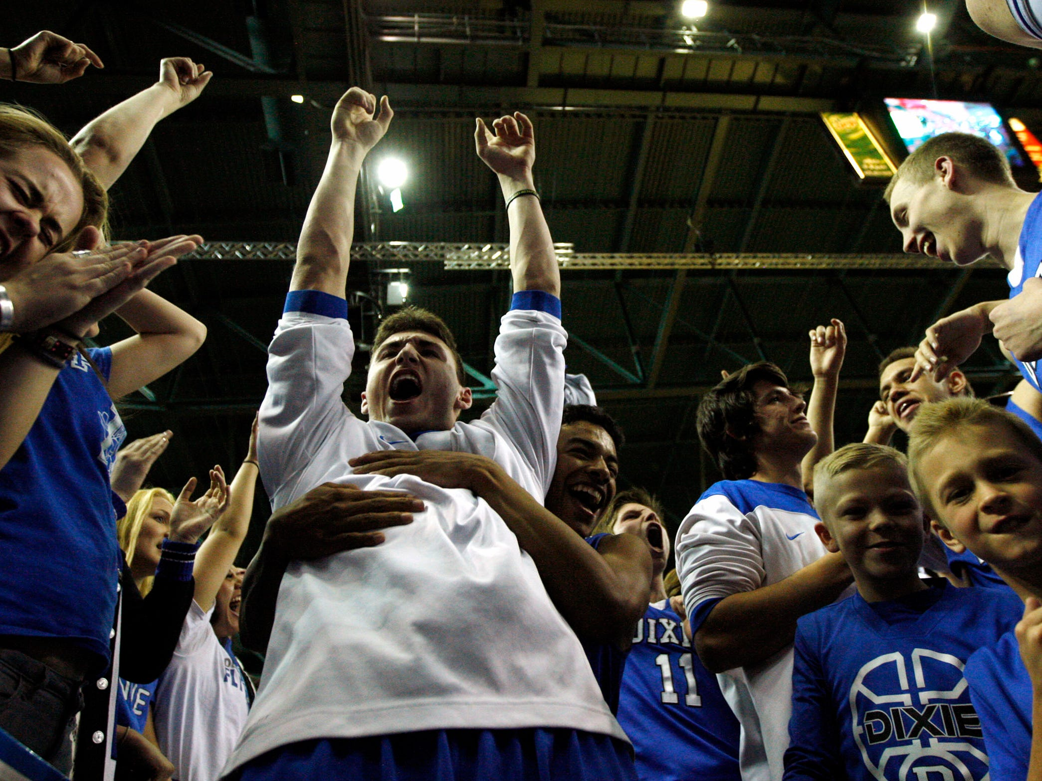 Dixie celebrates its win over Desert Hills in quadruple overtime in the 3A boys basketball semifinals at the Maverik Center in West Valley City Friday, Feb. 27, 2015.