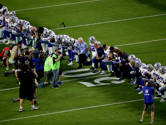 The Dallas Cowboys, led by owner Jerry Jones, center, take a knee prior to the national anthem prior to an NFL football game against the Arizona Cardinals, Monday, Sept. 25, 2017, in Glendale, Ariz. (AP Photo/Matt York)