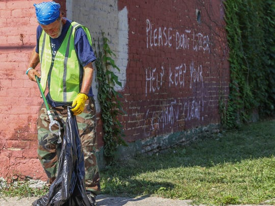 Chris Beck picks up trash while working for the Jobs Van program on Wednesday, July 11, 2018, in Over-the-Rhine. The new program run by City Gospel Mission pays homeless and panhandlers $9 an hour to pick up trash in an effort to reduce panhandling.