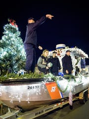 A Coast Guard member waves to the crowd from its float during the Chincoteague parade.