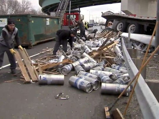 Crews clean up beer containers littering I-95 as the