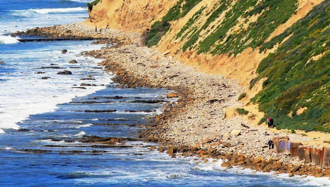 Waves roll onto boulders at the foot of a sea cliff near Royal Palms Beach in the San Pedro area of Los Angeles on March 26, 2017.