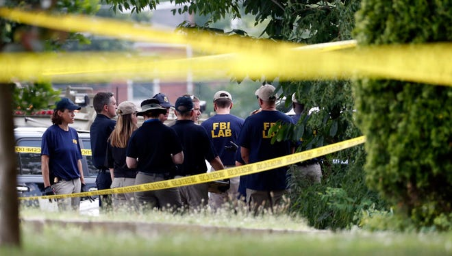 Investigators confer before looking for evidence around the baseball field in Alexandria, Va., that was the scene of a shooting involving House Majority Whip Steve Scalise of La., and others, during Congressional baseball practice on Wednesday.