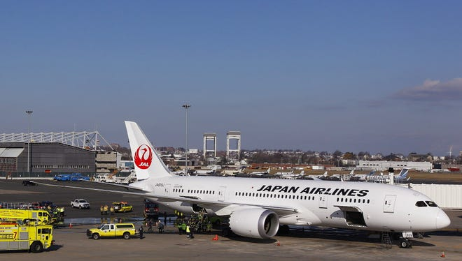 A Japan Airlines Boeing 787 Dreamliner is surrounded by emergency vehicles while parked at a terminal E gate at Logan International Airport in Boston on Jan. 7, 2013. The National Transportation Safety Board released a report Monday blaming the fire on a short circuit in a lithium-ion battery, and criticized Boeing supplier GS Yuasa for defects in manufacturing the batteries.