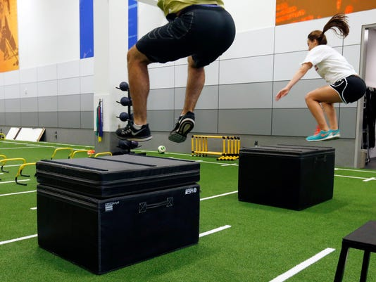 In this July 6, 2016 photo, Stephen Kalina and Haley Nielsen leap onto platforms at the Mayo Clinic in Minneapolis. Mayo's new facility for high-level conditioning with noted performance trainer EXOS isn't just for elite athletes anymore. The general public can sign up for workouts similar to what NFL prospects take part in preparing for the combine, and weekend warriors are getting in more than just a good sweat before going to the office. (AP Photo/Jim Mone)