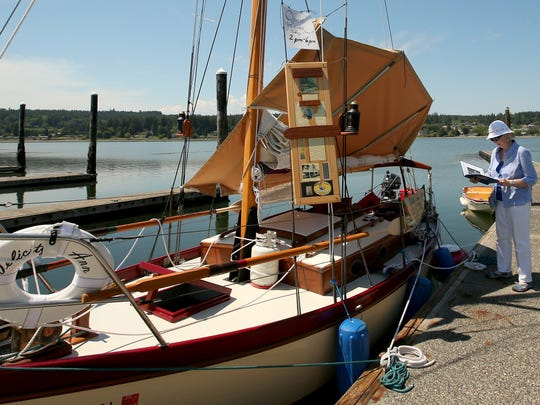 Sandra Cusick, of Poulsbo, reads about the history of the Felicity Ann on Tuesday at the Poulsbo Marina. The 23-foot vessel was restored at the Northwest School of Wooden Boatbuilding in Port Townsend.