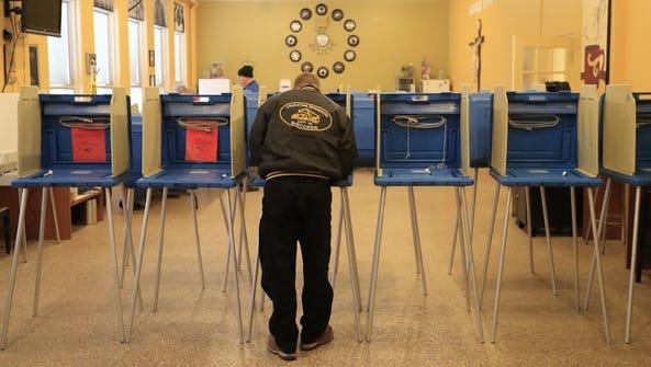 A voter fills out his ballot at St. Joseph's Parochial