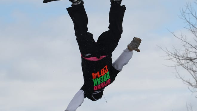 A snowboarder hangs upside down over Granite Peak Ski Area in Rib Mountain.
