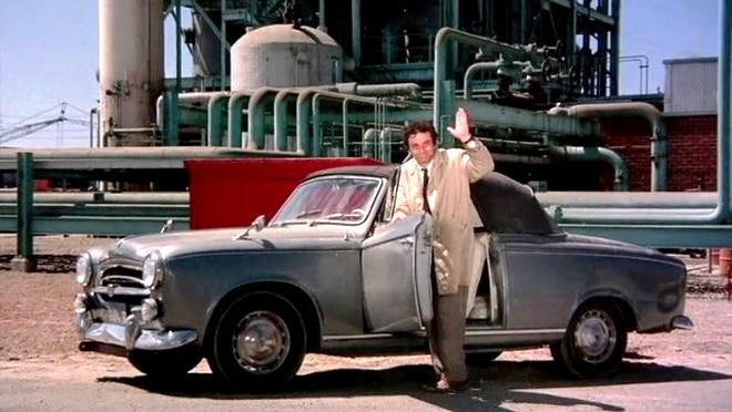 "Peter Falk poses with his ""sidekick"" 1959 Peugeot 403 Cabriolet (convertible) during a scene from the hit TV series ""Columbo."" Both NBC and ABC took part in its success during a 1971 to 2003 run."