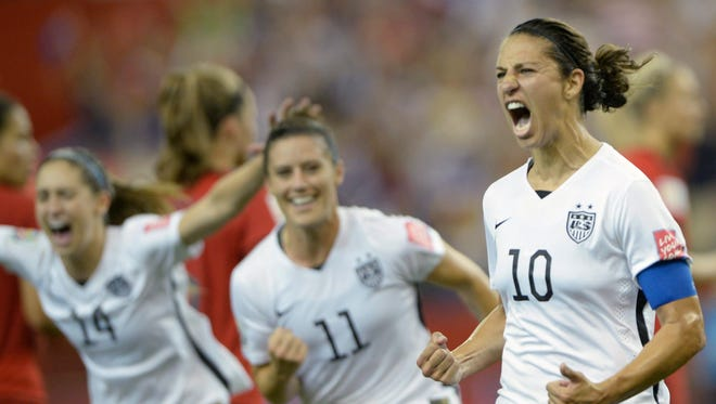 Carli Lloyd (10) of Team USA celebrates with teammates Ali Krieger (11) and Morgan Brian after scoring on a penalty kick against Germany in the semifinals of the Women's World Cup soccer tournament, Tuesday, June 30, in Montreal.