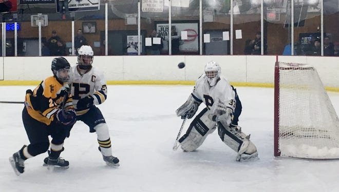 Pelham goalie Justin Ming and defenseman Gib Smith (24) keep an eye on a rebound in the second period of Sunday's 7-4 win over St. Anthony's at the Ice Hutch.