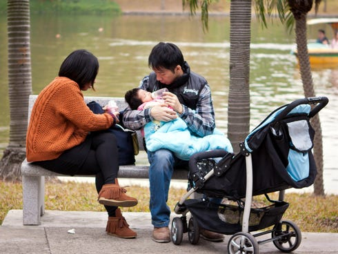 A young couple feed their baby at a park in Guangzhou city, China.