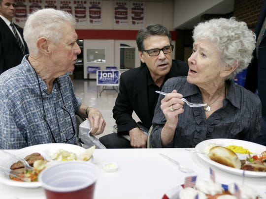 Texas Gov. Rick Perry talks with Dick Dale, left, and his wife Marguerite, right, of Algona, during a meeting with local party activists in July. Dick Dale died Friday at age 88.