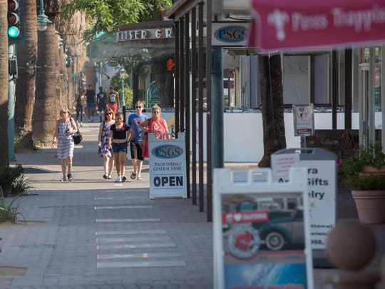 Shoppers and visitors stroll downtown on Palm Canyon Drive in Palm Springs on July 27, 2017.