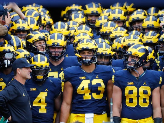 Michigan coach Jim Harbaugh leads his team into Kinnick