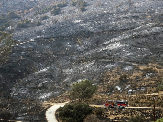 A fire engine drives past a burned area from a wildfire
