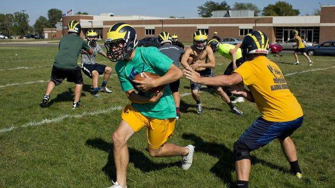 Senior AJ Garshott hands off the ball to senior Brendan Piper during football practice Thursday, September 17, 2015 at Algonac High School.