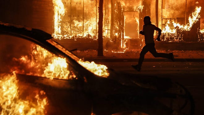 A protester runs past burning cars and buildings on Chicago Avenue, Saturday, May 30, 2020, in St. Paul, Minn. Fox News used this photo on its website to promote a package of stories on Seattle's protest zone, the Seattle Times reported. The network has since removed the photo, as well as other photos from Seattle that had been digitally altered, the newspaper reported.