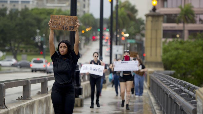 People protesting George Floyd's death walk east over the Royal Park Bridge on Friday.
