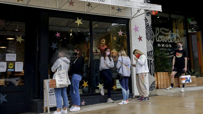Shoppers wait outside the Madewell store on South Congress Avenue during a Black Friday sale.