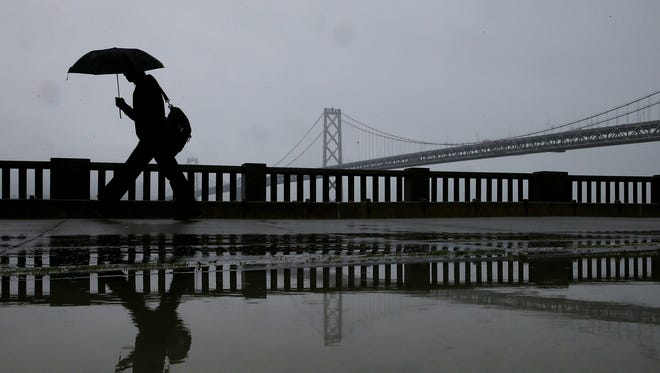 A pedestrian walks near the Bay Bridge on February 6, 2014, in San Francisco. California is getting a much-needed dose of rain and snow this weekend.