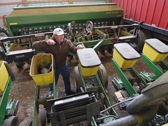 Drew Eckert works on his corn planter, preparing for