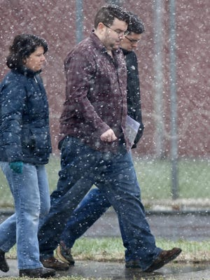 Suspended Colchester Police detective Tyler Kinney (center) leaves the Northwest State Correctional Facility in St. Albans on Monday, November 17, 2014.