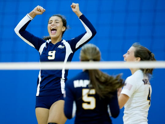 Naples' Lily Grasso (9), Shyanne Sannicandro (5), and Elyssa Glass (4) celebrate after a point is scored against Barron Collier High School in the Class 7A District 12 Championship game at Naples High School Thursday, October 20, 2016 in Naples.