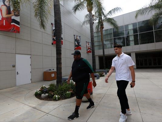 Filipino basketball player Kobe Paras, right, leaves the Cal State Northridge Matadome, after being introduced in Northridge, Calif., on Wednesday, May 31, 2017. Paras has transferred from Creighton to Cal State Northridge and will be eligible to play basketball for the Matadors in 2018-19. The 6-foot-6 guard returns to Los Angeles, where he played at Cathedral High before transferring to Middlebrooks Academy for his senior year. (AP Photo/Damian Dovarganes)