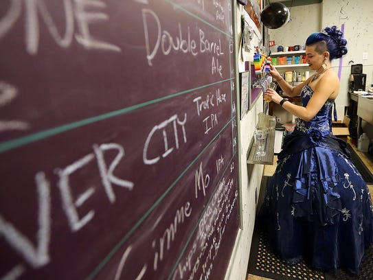 """Ashley Martinez pulls pints of beer for customers during her """"Nerdy 30"""" birthday party at her downtown Bremerton pub."""