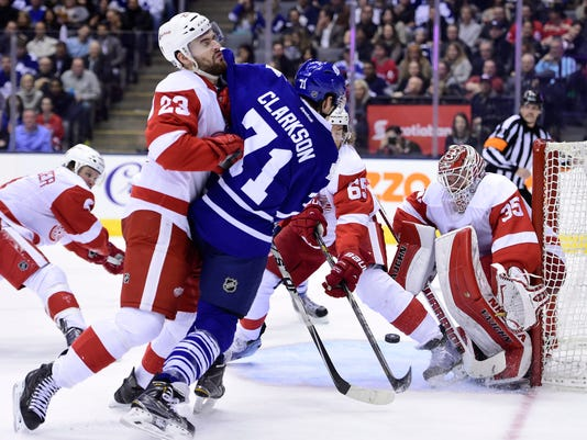 Detroit Red Wings' Brian Lashoff (23) hits Toronto Maple Leafs' David Clarkson (71) as he tries to get a shot on net during the second period of an NHL hockey game in Toronto on Saturday, Nov. 22, 2014. (AP Photo/The Canadian Press, Frank Gunn)
