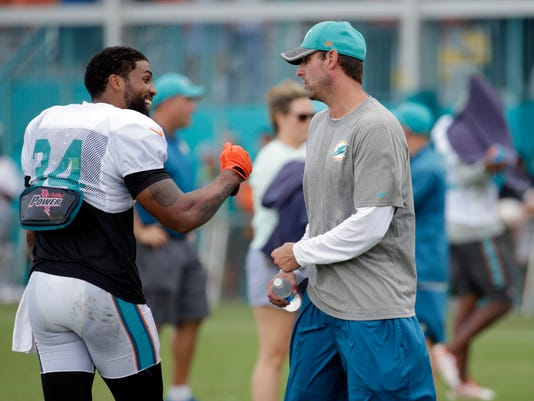 Miami Dolphins running back Arian Foster (34) talks with head coach Adam Gase, right, Tuesday, Aug. 16, 2016, after practice at NFL football training camp in Davie, Fla. (AP Photo/Lynne Sladky)