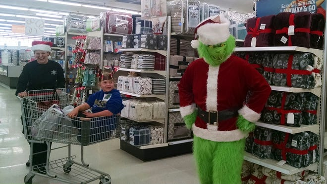 Cadet Robin Roe, left, poses for a photo with her shopping partner and the Grinch during the Shop With Your Cops event on Dec. 12 at Kmart in Farmington.