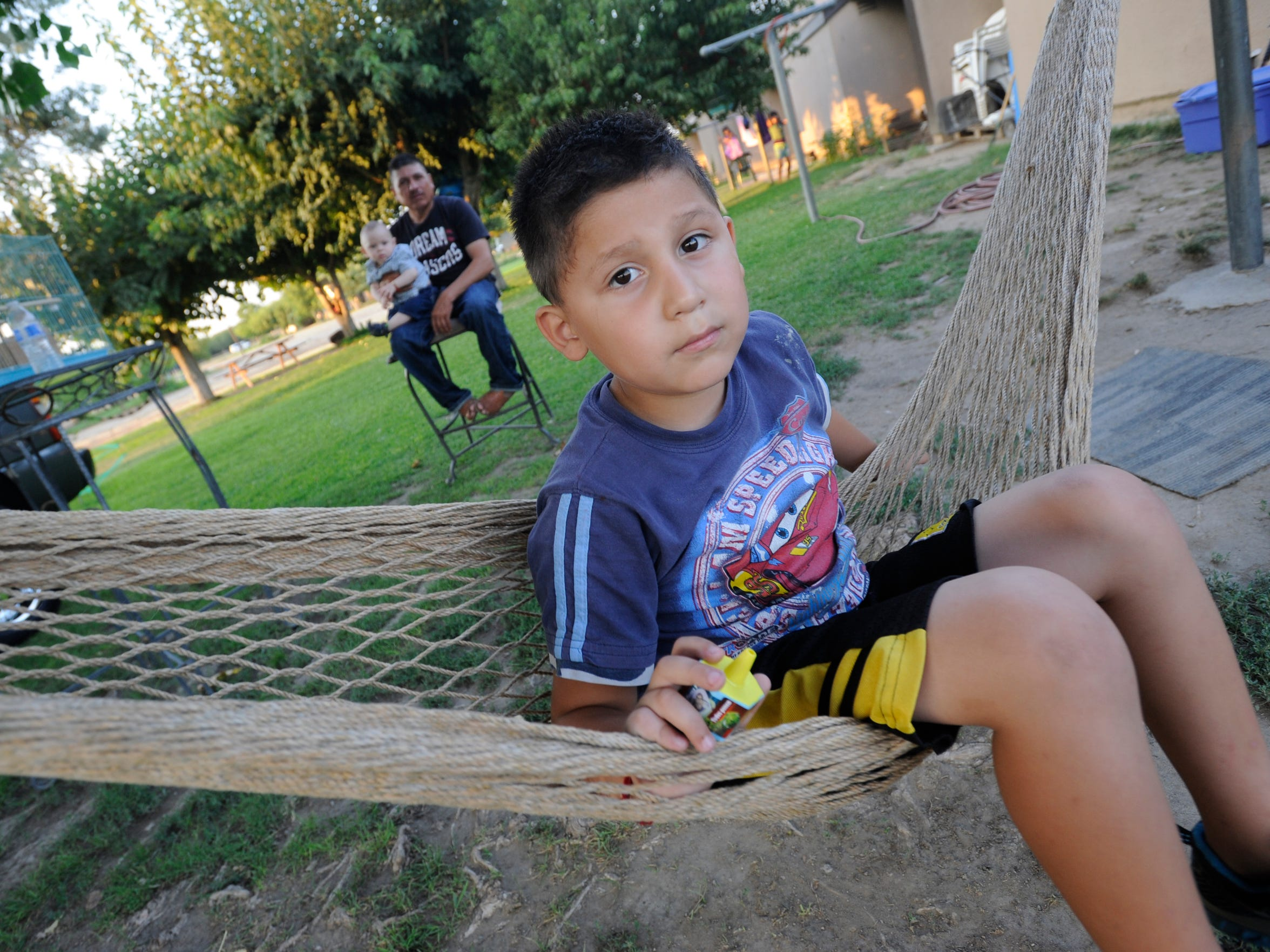 Oscar Sanchez, 5, swings on a hamoc as his dad Efrain Sanchez and his 8-month-old brother Efrain Edwin Sanchez relax outside their Linnell Farm Labor Center home on Tuesday.
