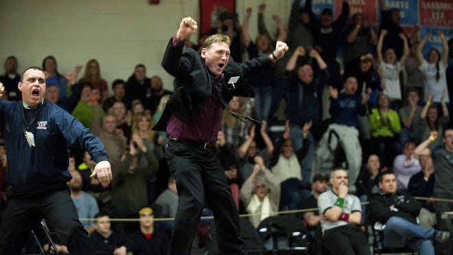 Mount Anthony coach Scott Legacy, center, celebrates after Ezra Caron's victory in the 182-pound state championship match on Saturday night.