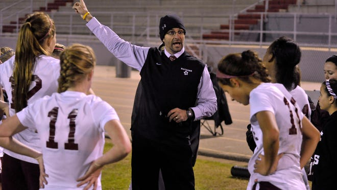 Navarre Raiders head coach Rob Simon talks strategy with his players during a break in their District 1-4A Championship game against the Niceville Eagles Friday night. Navarre went on to win the game on penalty kicks after a double-overtime found the two teams scoreless.