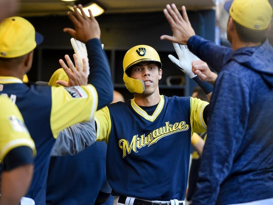 Christian Yelich celebrates in the dugout after hitting a solo home run.