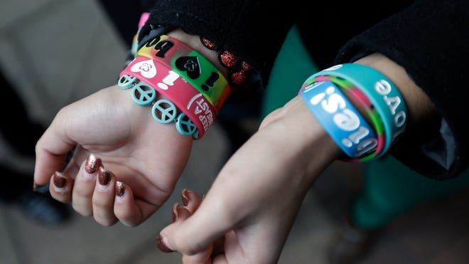 """Students Brianna Hawk, 15, left, and Kayla Martinez, 14, display their  """"I (heart) Boobies!"""" bracelets for photographers outside the U.S. Courthouse in Philadelphia in February 2013. The Supreme Court declined to hear the case, leaving intact a lower court decision overturning a ban on the bracelets."""