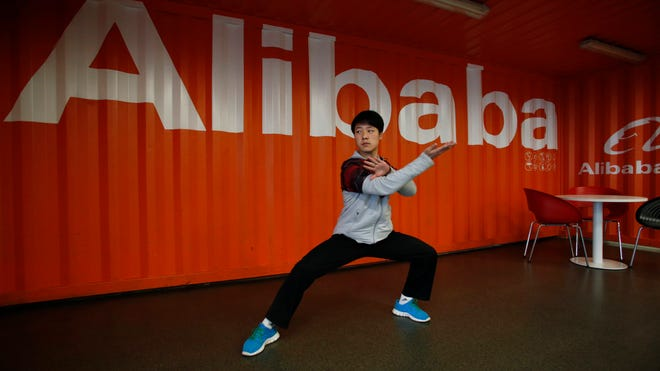 In this photo taken March 26, 2013, and made available March 11, 2014, a worker performs shadow boxing during an open day at the Alibaba Group office in Hangzhou in east China's Zhejiang province. Ten companies including Internet giants Alibaba and Tencent have been picked to invest in China's first five privately owned banks, the industry's chief regulator said March 11, 2014.