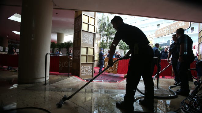 Fire department and hotel maintenance workers try to remove water from a section of the red carpet arrivals area  at the 71st annual Golden Globe Awards.